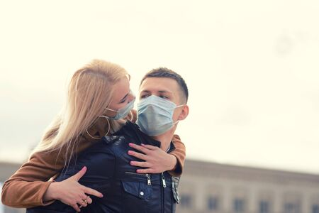 Couple in protective masks have a walk outdoors in the city near business building at quarantine time. Conception of coronavirus, covid.