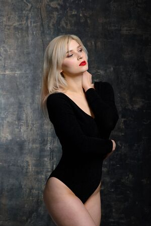 Young plump woman with bright makeup in black bodysuit is posing at dark background, isolated with copy space. Concept of xxxl fashion and junk food Standard-Bild