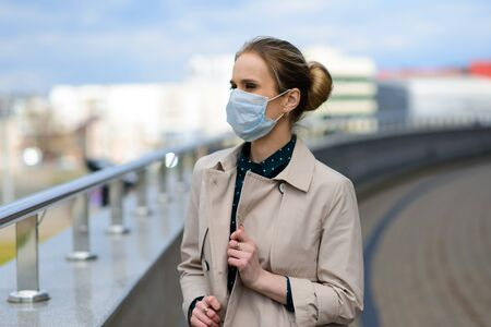 A young businesswoman wearing a health mask and talking on the phone in the city, isolation and quarantine concept