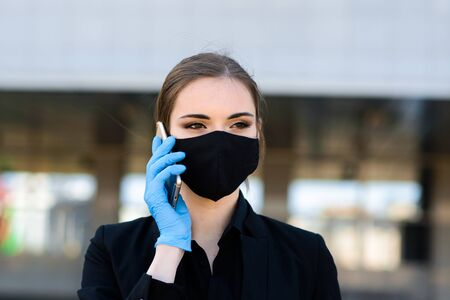 Beautiful businesswoman in a black suit in a black medical mask and gloves at the city in quarantine and isolation. Pandemic COVID-19. Image with selective focus