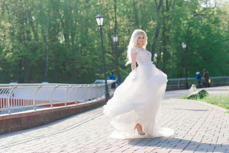 Young attractive blonde bride with curly hair walking in the park and smiling, concept wedding Banco de Imagens