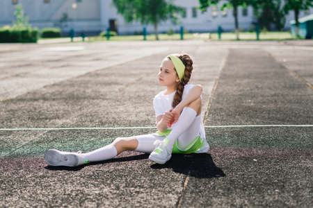 Girl jogging on a sunny summer evening, laying on treadmill, stadium, physical training, back to school, tired. Imagens