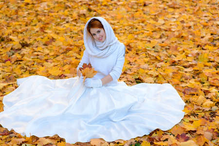 Portrait of a beautiful young redhead girl with flowers look attractive in a white dress on a background of autumn forest and leaves smiling.