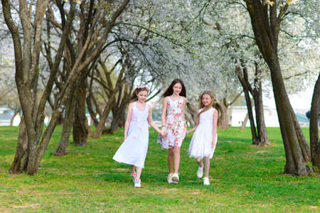 Three adorable girls in dresses hold hands in a circle holding hands. Spring, garden. 版權商用圖片
