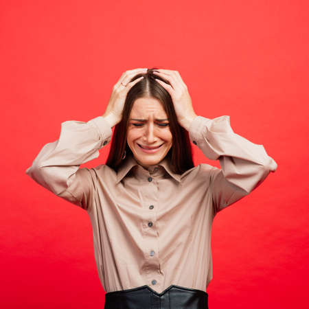 What is it. The female portrait isolated on red studio backgroud. The young emotional angry, scared woman looking at camera.The human emotions, facial expression concept. Trendy colors 写真素材