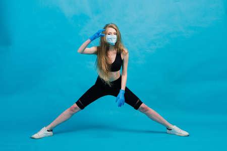 Fitness girl wearing medicine mask in fitness costume isolated on blue background. Training during quarantine, covid 19, corona virus. 免版税图像