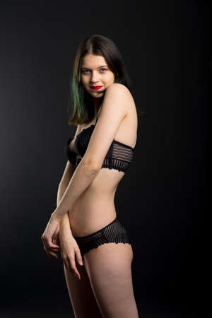 Vertical view photo beautiful shy lady in lace bikini boudoir bra panties. Tender slim shape isolated black background. Banque d'images
