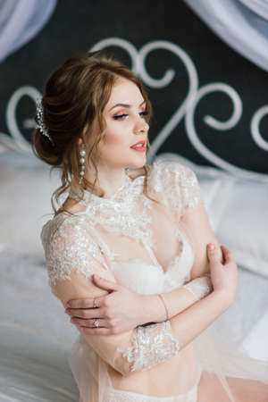 Beautiful young bride in a white lingerie. Last preparations for the wedding. The girl is waiting for the groom.