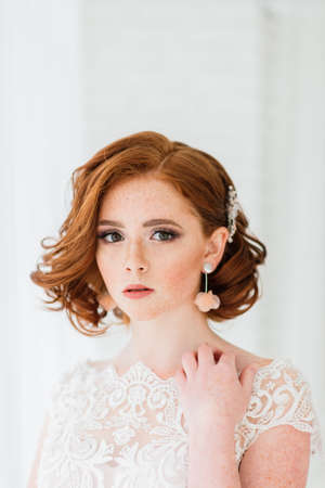 Portrait of red haired girl wearing wedding dress against a white and grey studio background. Banque d'images