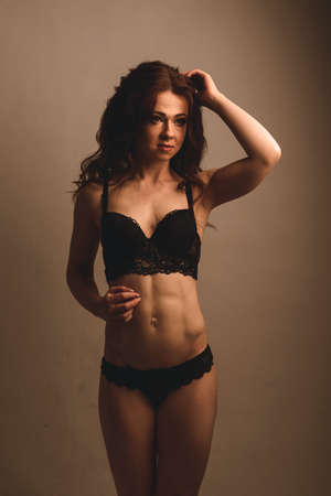 Fashionable young curly brunette sensual woman in sexy black lingerie in studio