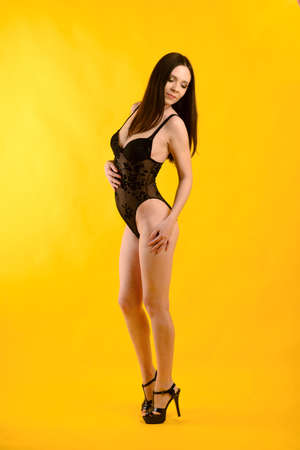 A sexy model posing in a black bodysuit againts a yellow background. Studio photo