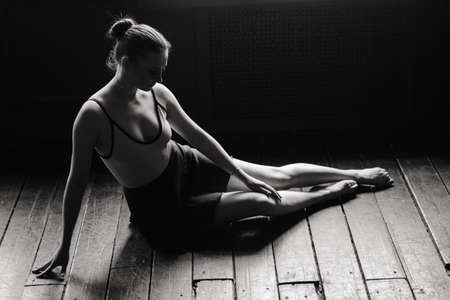 Beautiful young female classical ballet dancer on pointe shoes wearing a black leotard and skirt on a studio background