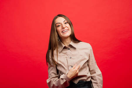 What is it. The female portrait isolated on red studio backgroud. The young emotional angry, scared woman looking at camera.The human emotions, facial expression concept. Trendy colors Stockfoto