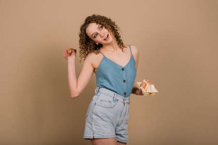 Studio shot of a cute curly woman holding an eggs - copy space on grey background. Emotional portrait