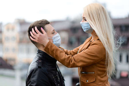 Couple in protective masks have a walk outdoors in the city near business building at quarantine time. Conception of coronavirus pandemic. Stock Photo