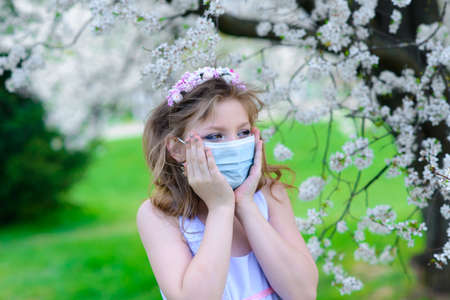 Lonely teenage girl wearing protection medicine mask against virus and allergy enjoying spring flower blossom in the garden