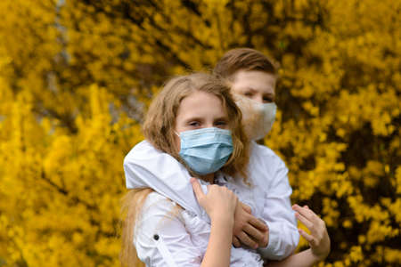 Children in a city park in a medical mask. Walking on the street during the quarantine period of the coronavirus pandemic in the Europe. Precautions and teaching children