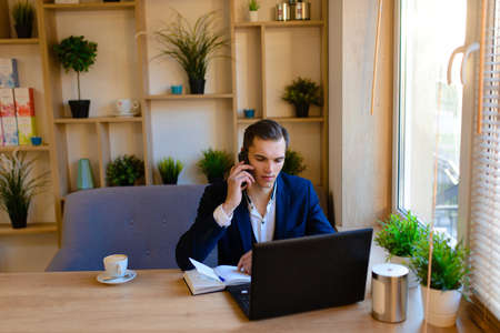 Young businessman in the caffee with mobile phone