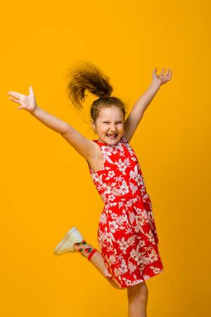 Happy carefree child emotions. Energetic joyful adorable little girl laughing at joke on yellow background in studio.