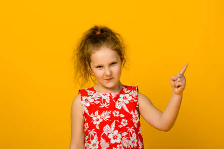 Angry little girl isolated on a over yellow background