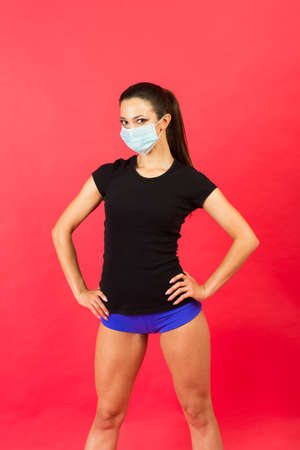 Shocked young fitness woman in sportswear sterile face mask working out isolated on yellow background studio portrait. Workout sport motivation lifestyle concept. Mock up copy space. Spreading hands Imagens