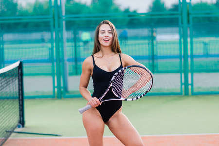 Beautiful young free sports fitness girl dressed in bodysuit, sneakers, with a smart and long legs, on a sports ground on a tennis court with a beautiful sky in the background