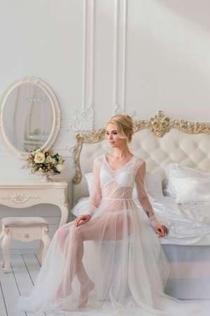 Conceptual wedding, the morning of the bride in the European style. Boudoir dress, fees in the interior Studio. White minimalism for bride