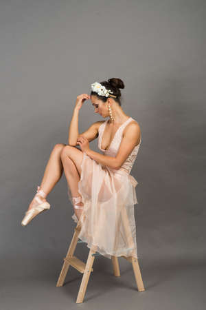 young beautiful ballet dancer in beige swimsuit posing on pointes on light grey studio background