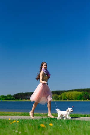 Young woman with her dog. Puppy white dog is running with it's owner. Concept about friendship and animal.