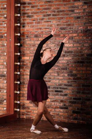 Ballerina in dark bodysuit, in dress in dark interior Studio. Wall of bricks, piano. Wooden floor. 写真素材