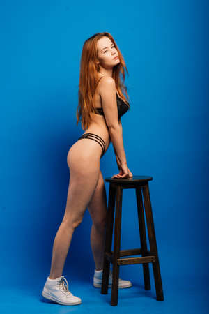 Glamorous curvy red head woman with a sexy body and small breasts posing in black lingerie on a blue studio background with vignetting