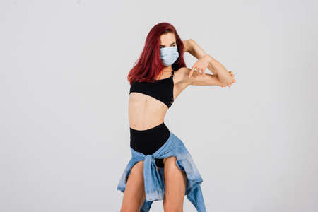Female dancer in the styles of strip plastic and pole dance with face mask on light background.