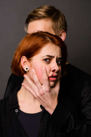 Desparate female with aggressive man in studio, domestic violence conception Archivio Fotografico