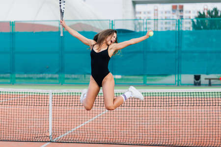 Beautiful young sport female dressed in a bodysuit on tennis court Banque d'images