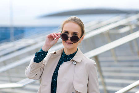 Young beautiful businesswoman with sunglasses, phone, laptop, cup of coffee in the city street 版權商用圖片