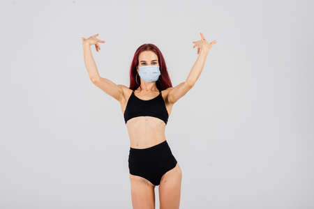 Female dancer in the styles of strip plastic and pole dance with face mask on light background. Stock Photo