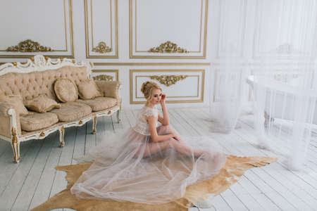 Morning of a beautiful young bride in a boudoir dress. Studio, interior.