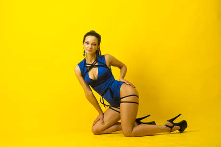 Sexy female pole dancer wearing blue bodysuit and high heels on a yellow background