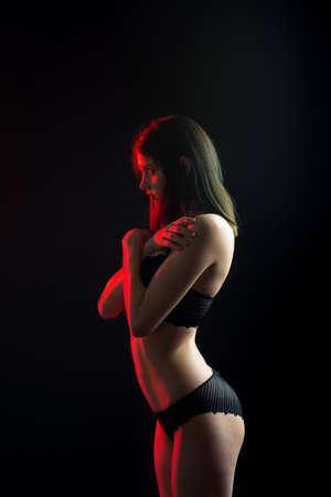 Cute brunette female model posing, wearing black underwear in studio