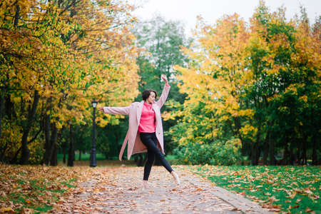 Ballerina dancing in nature among autumn leaves in fair coat. Banque d'images