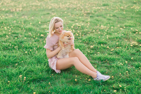 Attractive young woman holding dog spitz outside and smiling at camera. Concept about friendship between people and animals. Stok Fotoğraf