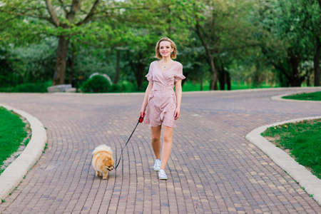 Attractive young woman holding dog spitz outside and smiling at camera, walking in the park. Concept about friendship between people and animals.