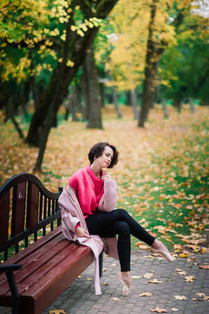 Young beautiful ballerina in fair coat and pointe shoes sit on the bench, rest outdoors in autumn park.