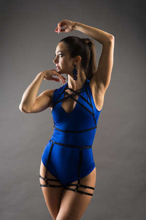 Sexy female pole dancer wearing blue bodysuit and high heels on a grey background