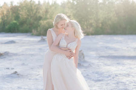 Beautiful couple walking on sand along a river bank on their wedding day