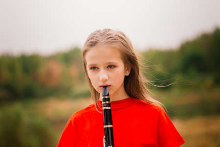 Young attractive girl playing clarinet in fall park