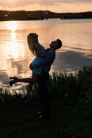 Silouette, loving couple on the lake during sunset