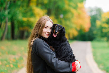 Young attractive woman holding her dachshund dog in her arms outdoors in sunrise in park at autumn time