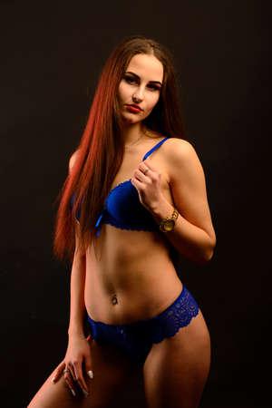 Beautiful woman in blue underwear on a dark background, perfect female body, studio shot Foto de archivo