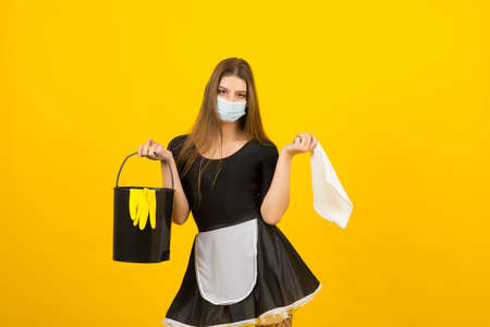 Beautiful sexy woman in maid clothes posing in studio in covid protective mask
